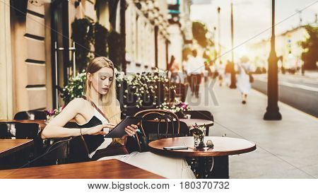 Cute adult blonde woman having online chat with her friend via digital tablet while sitting in street cafe alone beautiful lady surfing internet on her touch pad on sunny summer day in bar outdoors