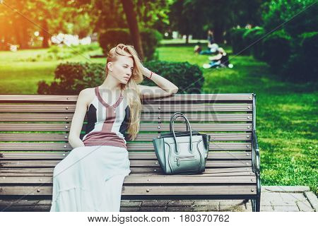 Tired charming blonde woman with long hair sitting on park bench with bag on sunny summer day and waiting meeting with friend with copy space for your advertising text message or promotional content