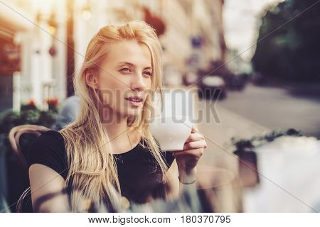 Adult blonde lady is drinking hot tea or coffee and thoughtfully looking aside from street cafe while enjoying her leisure time alone portrait of beautiful woman lunching in cafe during work break
