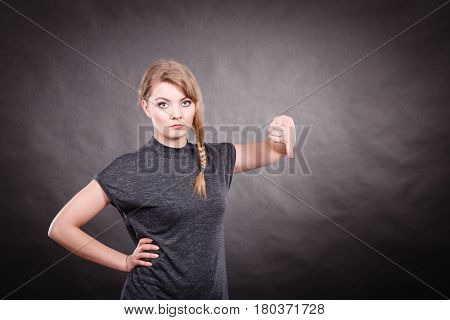 Bad and negative emotions and feelings concept. Blonde unhappy sad woman with thumb down. Depressed dissatisfied young girl portrait.