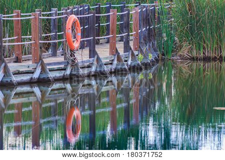 Close up of serene floating boardwalk with orange life preserver reflected in water