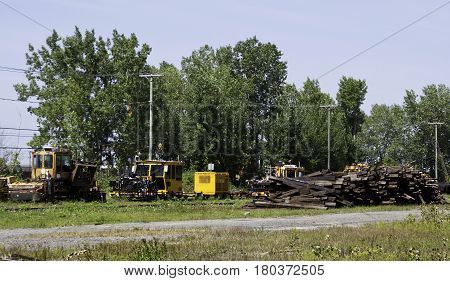 Montreal, Quebec, August 20, 2016 - Wide view of some railroad work vehicles beside a large pile of railroad ties in the CP Rail Train Yards in Cote Saint Luc in Montreal, Quebec, on a sunny day in August.