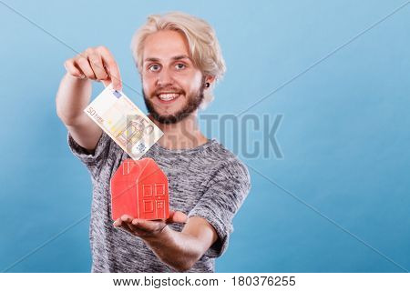 Man Puts Money Into House Piggybank