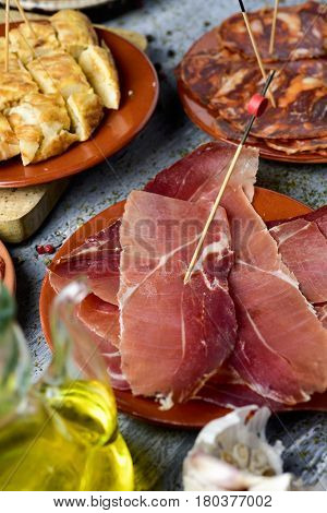 closeup of some plates with an assortment of different spanish cold meats, such as serrano ham and chorizo, a diced spanish omelette and a cruet with olive oil, on a rustic table
