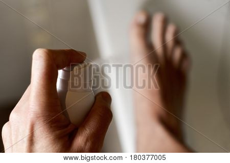 closeup of a young caucasian man young man in the bathroom applying deodorant spray to his feet