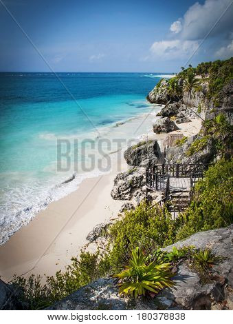The stunning blue water of the Caribbean sea seen from an elevated view on the cliffs above a white sandy beach in Tulum, Mexixco.