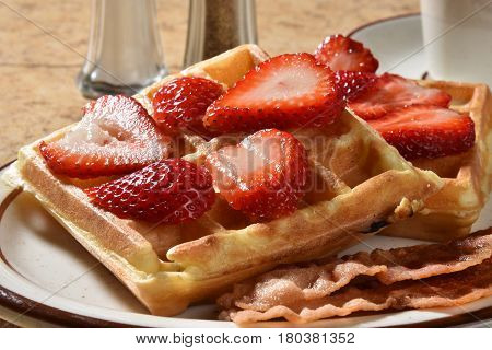 Buttered Belgian waffles with fresh strawberries and bacon