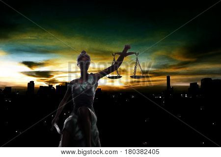 Silhouette of Lady Justice and city in dawn time