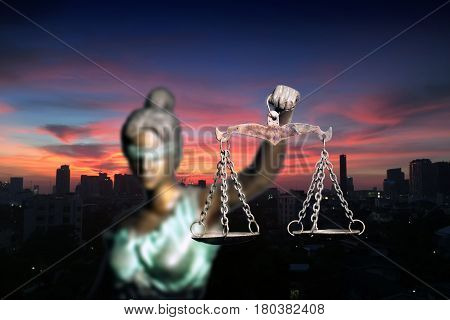 Lady Justice and city in dawn time