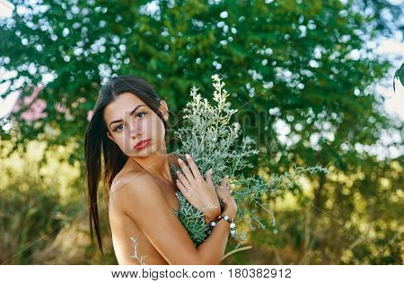 Beautiful young woman in summer on the background of nature
