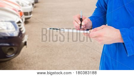 Digital composite of Mechanic with clipboard in blurry carpark