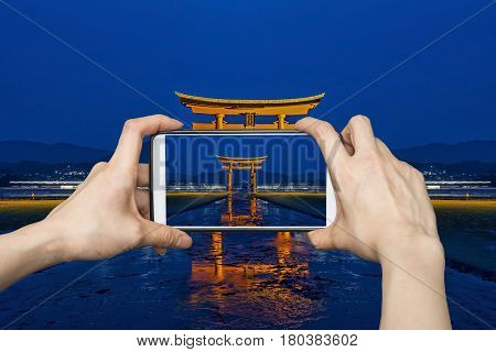 Tourist using smartphone taking a photo of Tori Gate in Hiroshima, Japan