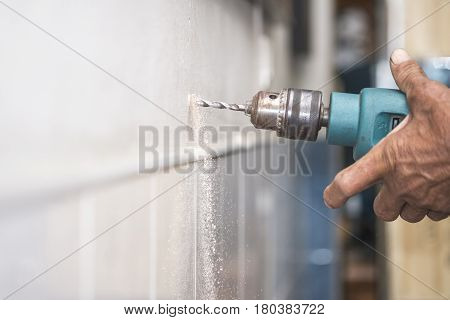 A man using an electric drill to bore a hole in the wall