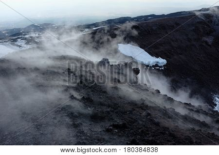 white smoke from volcanic ash of one of the hundreds craters in the Etna Park - Sicily