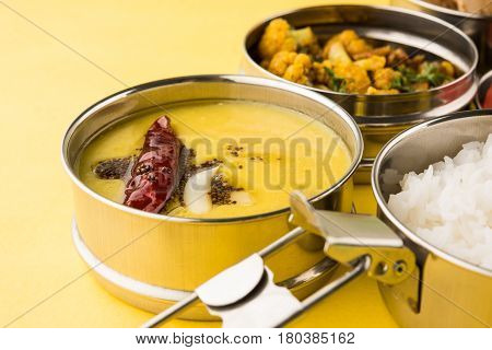 indian typical stainless steel lunch box or tiffin with north indian or maharashtrian food menu like chapati//roti, dal tadka, white rice and aloo / potato sabji / gobi or cauliflower sabji with salad