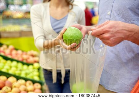 shopping, food, sale, consumerism and people concept - close up of couple buying apples at grocery store or supermarket
