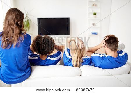 friendship, sport and entertainment concept - friends or football fans watching soccer on tv at home