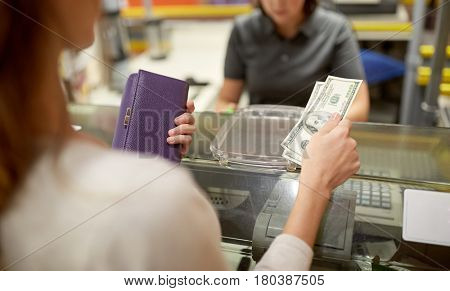shopping, payment, consumerism and people concept - woman paying money and cashier at store cash register