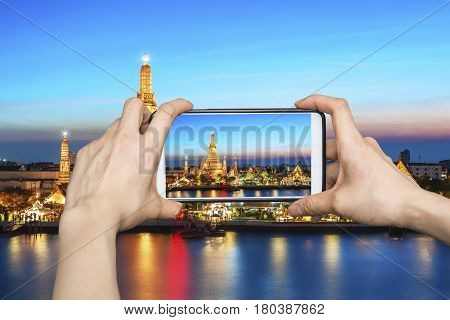 Tourist using smartphone taking a photo of Wat Arun at sunset, Bangkok, Thailand