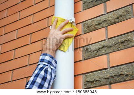 Man cleaning white pvc rain gutter system downspout pipeline. Cleaning White Gutters. Guttering.