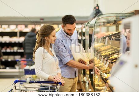 food, sale, consumerism and people concept - happy couple with shopping cart at grocery store or supermarket baking department buying buns or pies