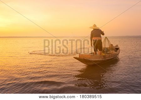 Asian Fisherman With Wooden Boat Throwing A Net For Catching Freshwater Fish In Nature River In The