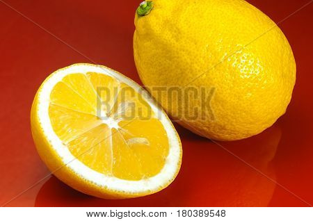 Lemon. A whole lemon and cut in half on a red background. Prevention of colds. Flu