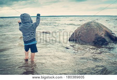 Baby boy barefoot are walking on the beach in water. Child on vacation in summer at the sea on bad weather