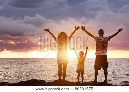 Happy family of father, mother and young son having fun at sunset beach. They greetings sea and sun