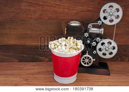 Popcorn bucket and music box in the form of an old movie camera on a wooden background