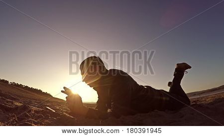Portable console. Man lies on sand and plays in the portable console at sunset sunlight
