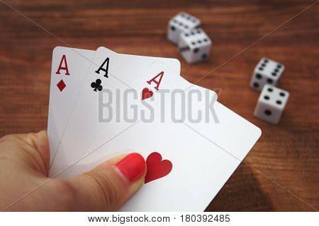 cards in poker player hand on a wooden background