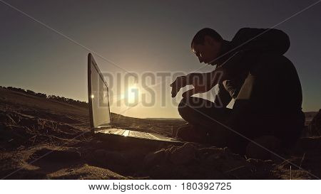 man businessman freelancer working behind laptop sitting on beach freelancing silhouette in sun