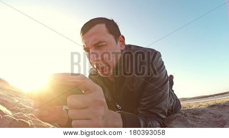 Portable console. Man lies on the sand and plays in portable sunlight console at lifestyle sunset