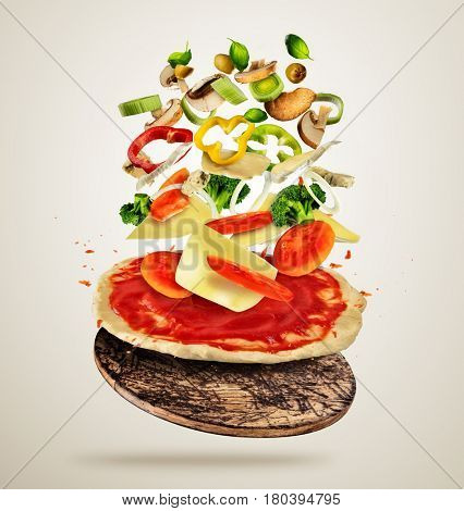 Concept of flying ingredients with pizza dough, isolated on creamy background. Food preparation, fresh meal ready for cooking