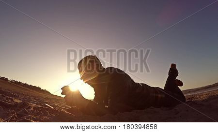 Portable console. Man lies on sand and plays in the portable console at sunset sunlight lifestyle