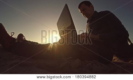 man businessman freelancer working behind laptop sitting on beach silhouette in sun freelancing