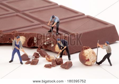 Miniature people Workers produce chocolate chips. isolated on white
