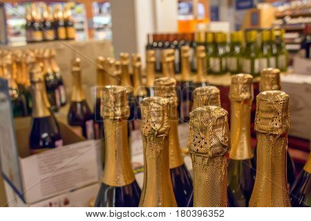 Closeup of neck and cap golden champagne bottles in grocery store