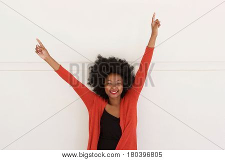 Happy Young African Woman With Arms Raised By White Wall