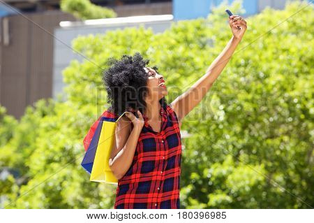 Happy Woman With Shopping Bags Taking Selfie Outside