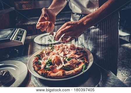 Food concept. Preparing traditional italian pizza. Chef in uniform decorate ready dish with green rucola herbs, ham, salami and prosciutto in interior of modern restaurant kitchen. Ready to eat.