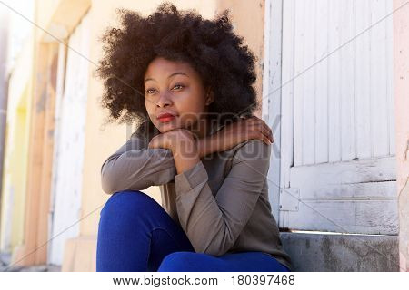 Young Woman Sitting On Steps Outside Door Looking Serious