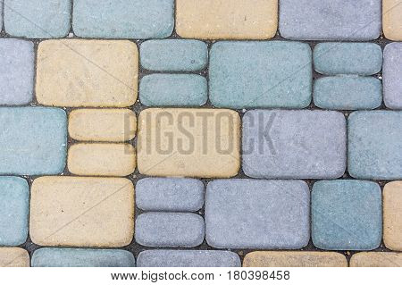 Texture of road surface with colorful blue and yellow pave stones