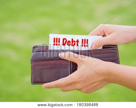 Women Hands taking out debt paper from wallet on the green grass field