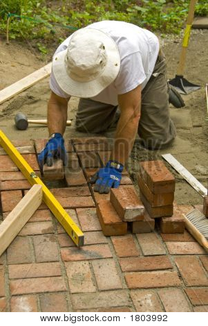 man laying a brick patio sand tools