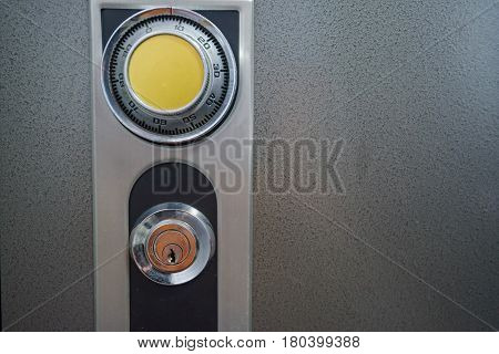 Closeup of combination safe with yellow knob and keyhole
