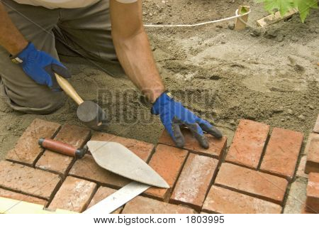 detail of man laying brick patio sand