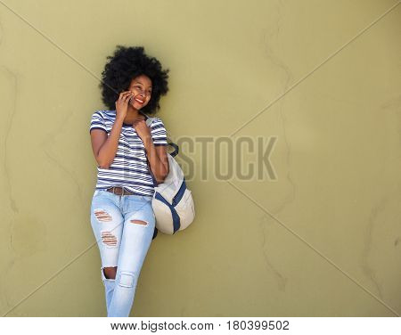 Happy Woman Talking On Smart Phone By Wall With Bag