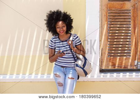 Smiling Woman Standing With Mobile Phone Outside House